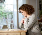 Счастливая женщина, глядя на компьютере дома — Стоковое фото