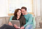 Happy couple sitting on couch looking at computer tablet — Stock Photo