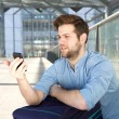 Man looking at mobile phone with confused expression — Stock Photo #72847509