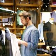 Mandsome young man shopping for clothes at shop — Stock Photo #72847679