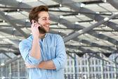 Smiling man enjoying conversation on cell phone — Stock Photo