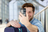 Young man holding mobile phone and taking selfie — Stock Photo