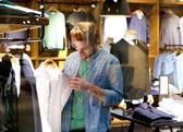 Happy man shopping for clothes at clothing store — Stock Photo