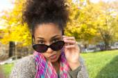 Young woman peeking over sunglasses — Stock Photo