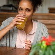 Young african american woman drinking orange juice — Stock Photo #73941507