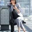 Smiling business woman reading text message on mobile phone — Stock Photo #75209779