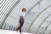 Бизнес женщина пешеходного и глядя на мобильный телефон — Стоковое фото