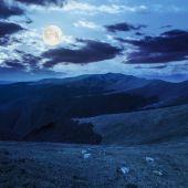 Stones on the hillside of mountain range in full moon light — Stock Photo