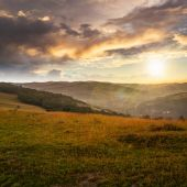 Field in mountain near home at sunset — Stock Photo