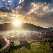 Mountain village in fog on sunrise — Stock Photo