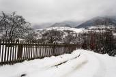 Snowy road to village in mountains — Stock fotografie