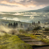 Steps down to village in foggy mountains at sunrise — Stock Photo