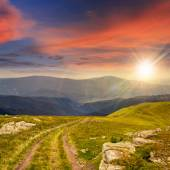 Road among stones on the hillside at sunset — Stock Photo
