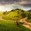 Cross road on hillside meadow in mountain at sunset — Stock Photo #61254521