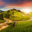 Cross road on hillside meadow in mountain at sunset — Stock Photo #61254599