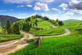 Cross road on hillside meadow in mountain — Stock Photo