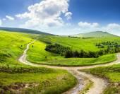 Cross road on hillside meadow in mountain — Stock Photo