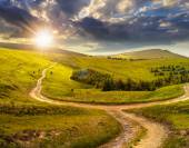 Cross road on hillside meadow in mountain at sunrise at sunset — Stock Photo