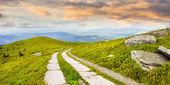 Road on a hillside near mountain peak at sunrise — Stock Photo