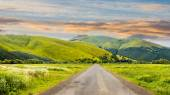 Abandoned road through meadows in mountain at sunrise — Stock Photo