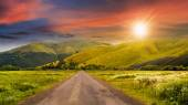 Abandoned road through meadows in mountain at sunset — Stock Photo