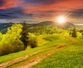 Road on hillside meadow in mountain at sunset — Stock Photo