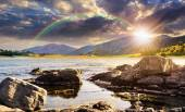 Lake with boulders in mountains at sunset — Stok fotoğraf