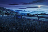 Fence on hillside meadow in mountains at night — Stock Photo