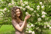 Beautiful girl with flower bush in park — Stock Photo