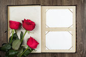 Photo album and roses on wood background — Foto de Stock