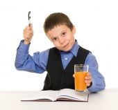 Schoolboy drinks juice at a desk with diary and pen — Stock Photo