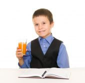 Schoolboy drinks juice at a desk with diary and pen — Foto de Stock