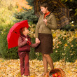 Woman and little girl in autumn park with apple basket — Stok fotoğraf #55898445