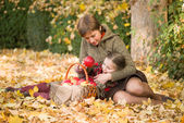 Woman and little girl in autumn park with apple basket — Stock Photo