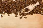 Coffee seeds with wooden shovel on wood background — Stock Photo