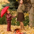 Woman and little girl in autumn park with apple basket — Stock Photo #56525905