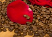 Red rose on coffee seeds and wooden background — Stockfoto