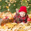 Little girl in autumn park with apple basket — Stock Photo #56727283