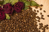 Dry red roses on coffee seeds and wooden background — Foto de Stock