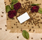 Blank sheet and dry red roses on coffee seeds — Stock Photo