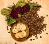 Trockene rote Rosen und Cookies auf Kaffee Samen — Stockfoto