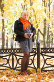 Pregnant woman in autumn park — Stock Photo