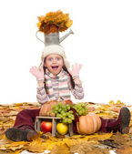 Girl with fruits and vegetables on autumn leaves — Stock Photo