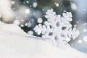 Big snowflake toy in snowdrift — Stock Photo