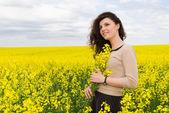 Girl portrait in yellow flower field — Stock Photo