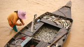 Many fish on boat with fisherman's woma — Stock Photo