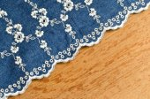 Jeans fabric with white flower embroidery laid over plywood back — Stock Photo
