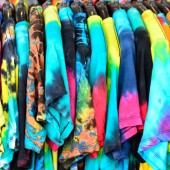 Colorful dyed t-shirt on hangers — Stock Photo