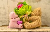 Couple of cute bear dolls holding roses bouquet — Stock Photo