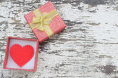 Red heart in gift box on grunge wood background in vintage style — Stock Photo